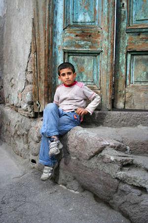 disadvantaged: poor child sitting at doorstep