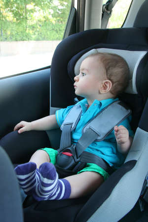 Baby in car seat for safety, looking outside
