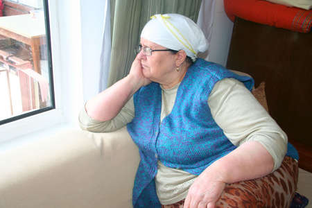 old lady thinking her memories at window photo