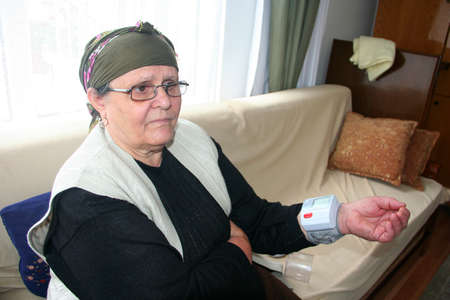 old lady measuring blood pressure at home  photo