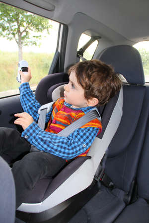 Baby in car seat for safety, playing with toy car Фото со стока