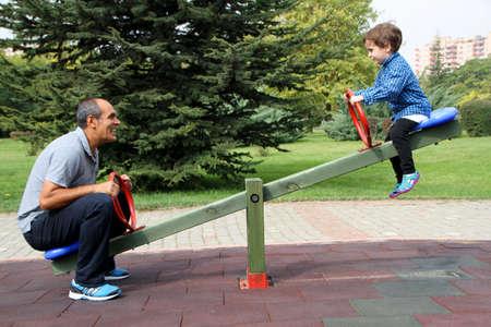 幸せな家族の遊び場、公園でシーソーを楽しむ