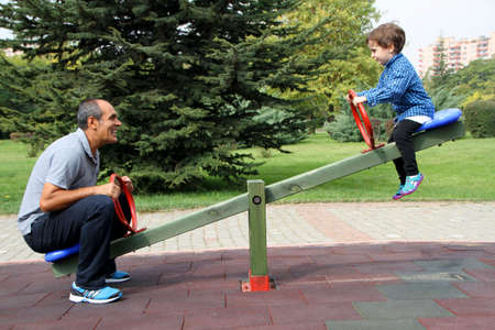 Happy family enjoying seesaw at the playground in the park 스톡 콘텐츠