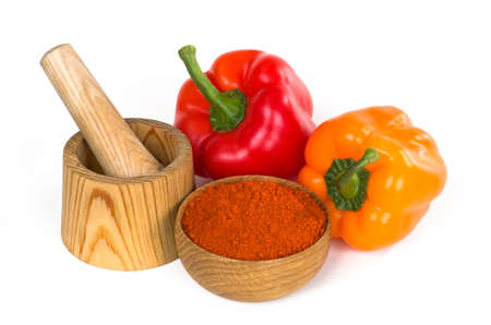 crushed red peppers: still life with bell pepper and paprika powder in a wooden bowl on white background Stock Photo