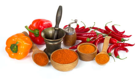 thereof: still life with paprika and chili powder ground in a wooden bowl and spoon on white background