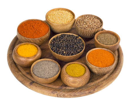 thereof: variety of spices and seasonings in wooden bowl on a wooden stand on white background