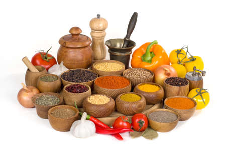 various spices and herbs in wooden bowl on white background