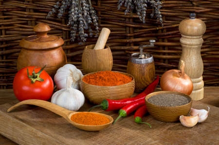 Still life with pepper and garlic with wooden utensils on a wooden table Stock Photo