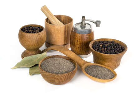 still life with black pepper and wooden utensils on white background Stock Photo