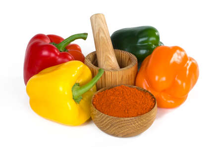 still life with bell pepper and paprika powder in a wooden bowl on white background Stock Photo