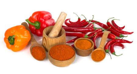 still life with paprika and chili powder ground in a wooden bowl and spoon on white background