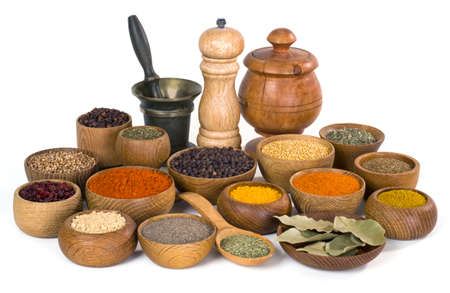 thereof: various spices and herbs in wooden bowl on white background