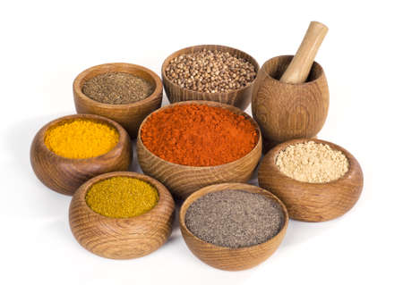 thereof: variety of spices and seasonings in wooden bowl on white background