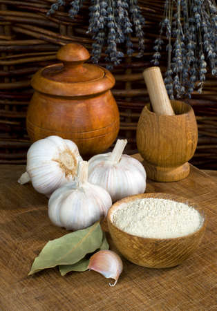 Still life with garlic dry ground and wooden utensils on the wooden table