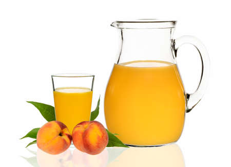 peach juice in a glass and carafe with peaches on a white background photo