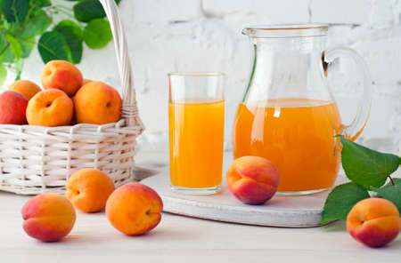 Apricot juice in glass and decanter with ripe apricots on wooden table on background of white brick wall with green leaves. Zdjęcie Seryjne