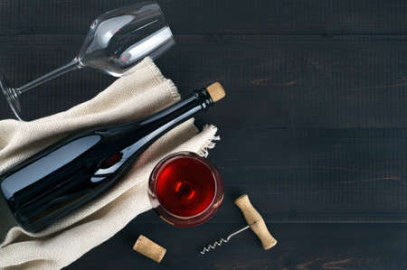 Wine bottle, wine glasses, corks and corkscrew on dark wooden background.  Top view, copy-space.