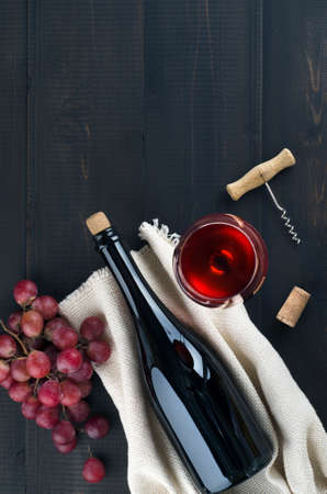 Bottle and glass of wine, bunch of pink grapes and corkscrew on dark background.  Top view, copy-space.