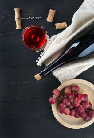 Bottle and glass of wine, bunch of pink grapes in plate  and corkscrew on dark background.  Top view, copy-space. 스톡 콘텐츠