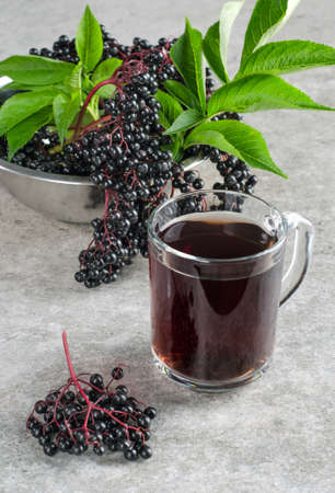 Clusters of ripe elderberry berries with green leaves and a drink in a glass on a gray background.