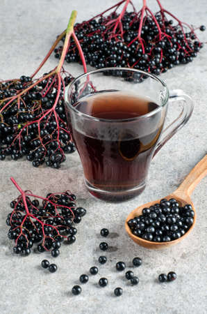 Bunches with ripe elderberry berries with a wooden spoon and drink in a glass on a gray background.