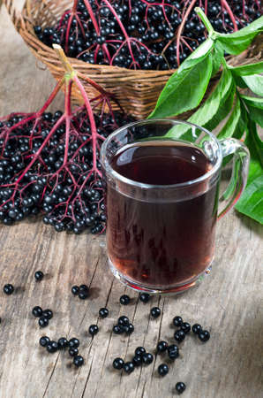 Bunches with ripe elderberry berries with green leaves and a drink in a glass on a wooden background. Rustic style.