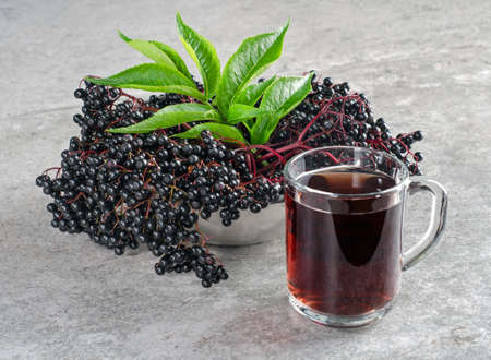 Clusters of ripe elderberry berries with green leaves and a drink in a glass.