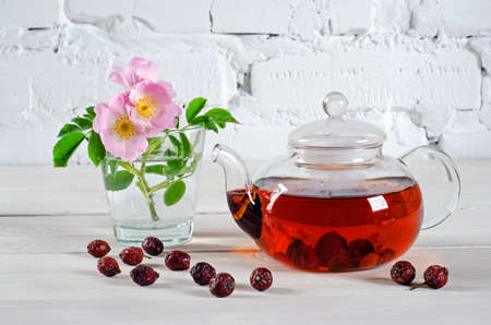 Тeapot tea with rosehips and rose hip flowers on white wooden table with copy space for your text