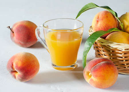 Peach juice in a glass beaker and juicy ripe peaches on a white table.