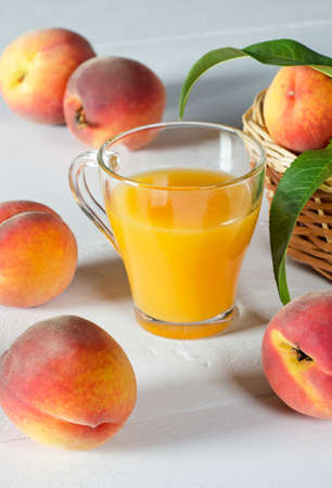 Peach juice in a glass beaker and ripe peaches on a white table.