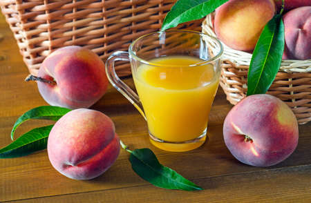 Peach juice in a glass beaker and ripe peaches on a wooden table. Rustic style. 版權商用圖片