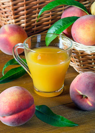 Peach juice in a glass beaker and peaches on a wooden table. Rustic style. 版權商用圖片