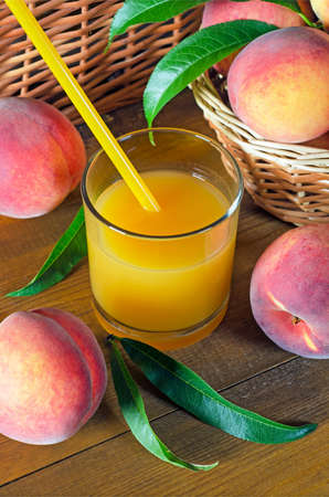 Peach juice in a glass beaker and juicy ripe peaches on a wooden table. Rustic style.