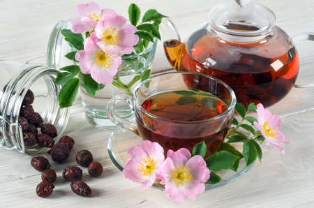 Rosehip flowers and cup of tea with rosehips on white wooden table. Ð¡lose up.