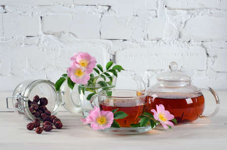 Ð¡up rosehip tea and teapot with rose hip flowers on white wooden table with copy space for your text.