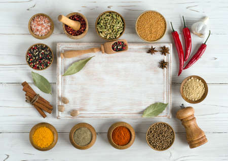 Set of various spices and herbs around an empty cutting board on white wooden background. Top view copy space. Flat lay