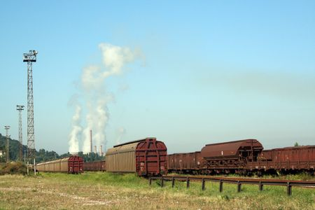 Trains with industry chimneys in background photo