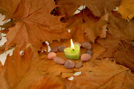 Background made of autumn leaves, heart shaped candle and stones Stock Photo