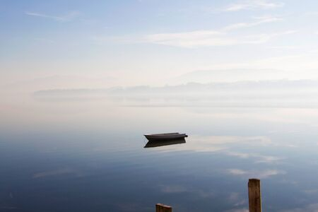 Boat on lake with reflection of sky and fog