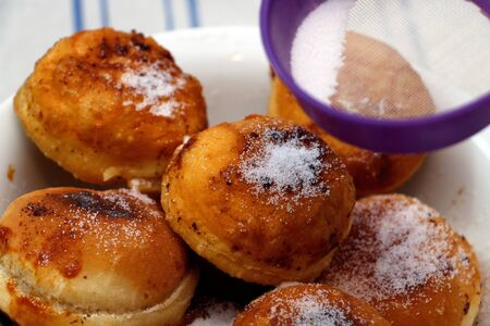 Powdering donuts with strainer