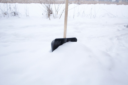 Snow shovel in garden Stock Photo