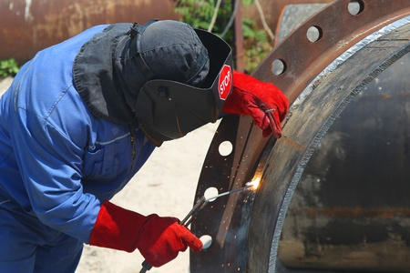 soldador: Un soldador de trabajo con un tubo metálico