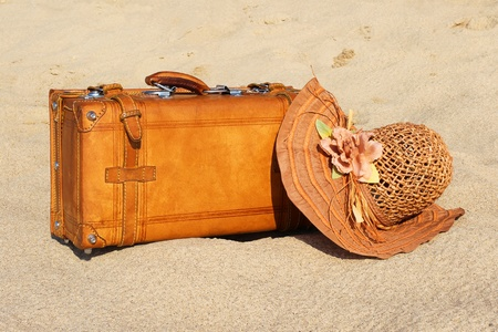 Leather suitcase and bonnet on the sand