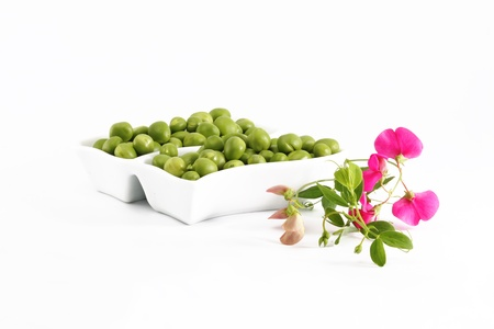 Green Peas and a branch with flowers on a white background photo