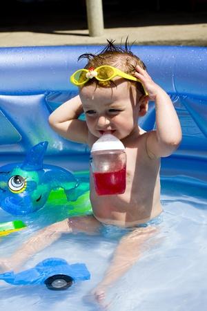 hot temper: El ni�o estaba sentado en la piscina usan gafas, en juguetes de agua clara
