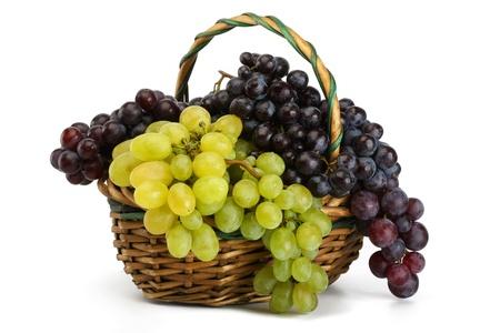 pasas: Racimos de uvas de amarillos y negros en una cesta sobre un fondo blanco