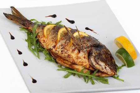 plato de pescado: pescado frito con hierbas frescas y lim�n