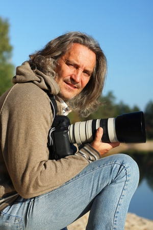 Portrait of a tanned man with a camera on the river on a sunny day photo