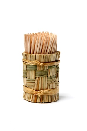 wooden toothpicks in a stand of straw on a light background Stock Photo - 10782489