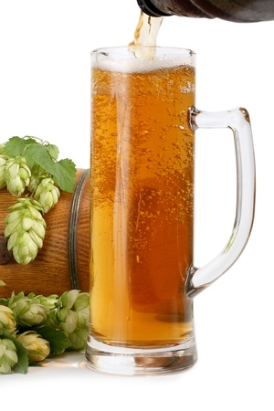 Beer is poured into a glass, a wooden barrel and flower hops, isolated on a white background photo
